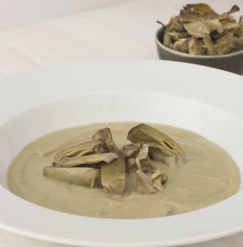 Ración de la receta de crema de alcachofas con alcachofas confitadas en plato hondo blanco. Acompañando vol verde con chips de alcachofas. Todo sobre mantel blanco.