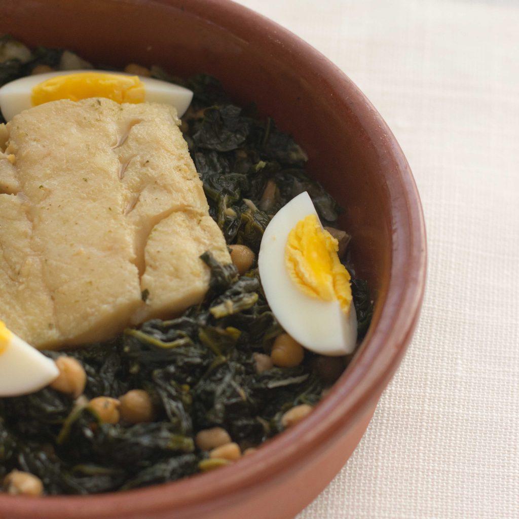 Cazuela de barro con ración de bacalao con espinacas, garbanzos y huevos duros. Sobre mantel blanco.