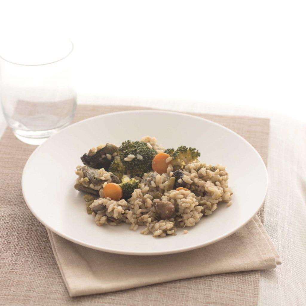 Ración de la receta de paella de verduras en plato blanco (arroz con alcachofas, zanahorias, brócoli, champiñones). Mantel color beige y vaso transparente.