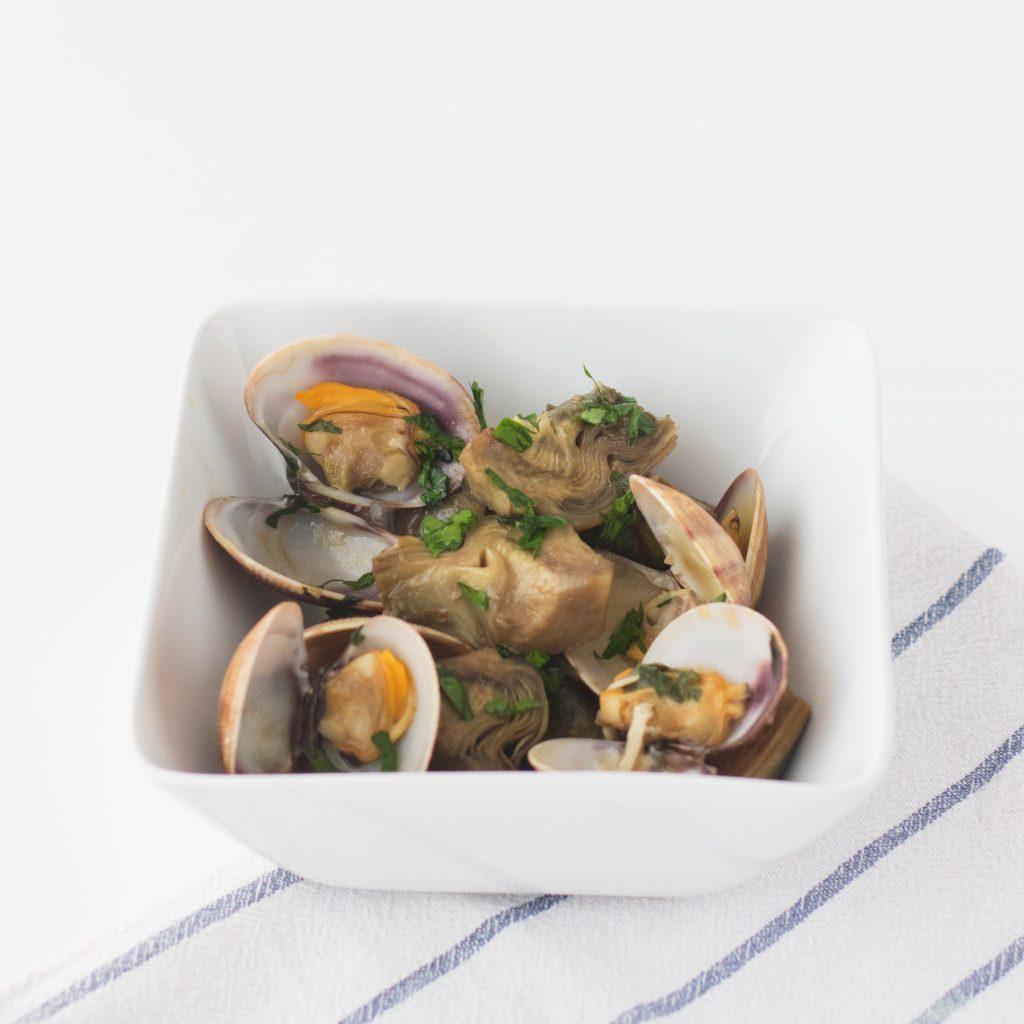 Bol blanco sobre tela rallada blanca y azul. Ración de la receta de alcachofas con almenjas y perejil.