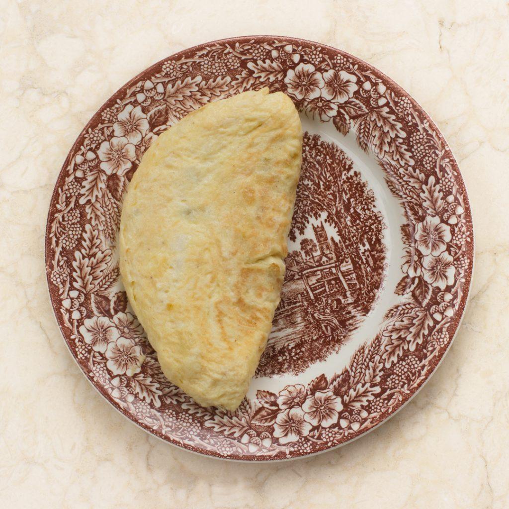 Plato rústico en mesa de marmol. En el plato tortilla de ajos tiernos y bacalao hecha en forma de media luna.